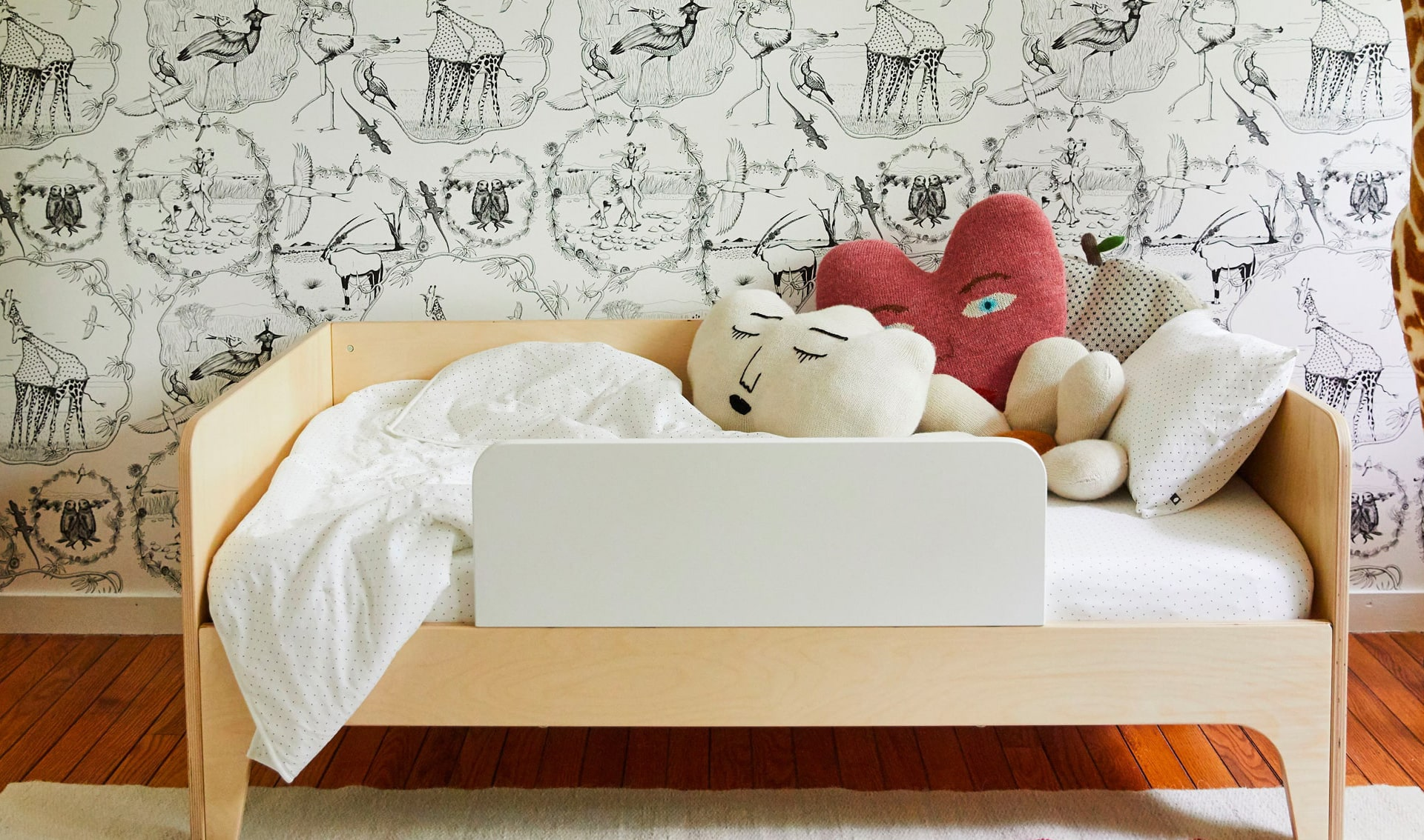 Cute Kids' Bedroom with Wallpaper and Giraffe Stuffed Animal