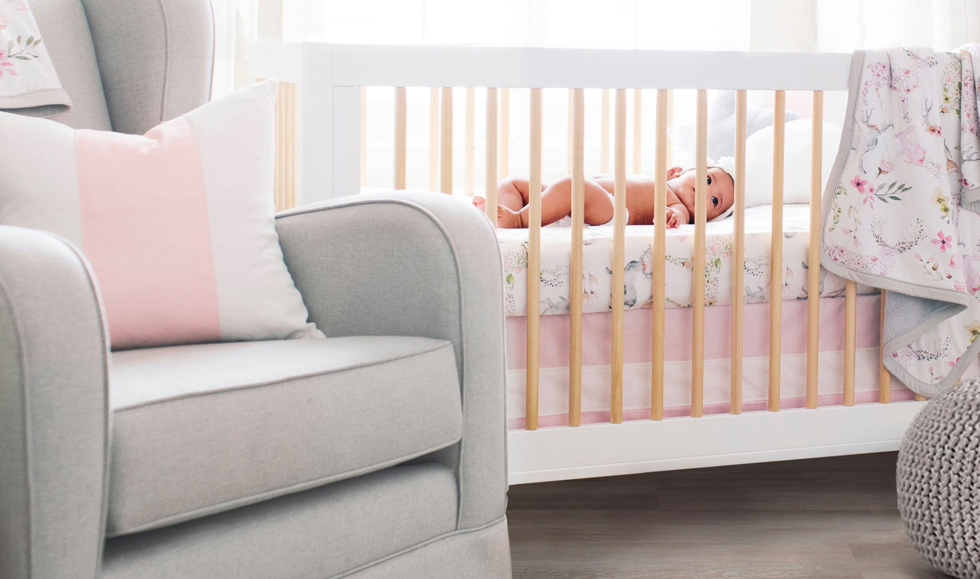 Baby in Crib in a Pink and Grey Nursery
