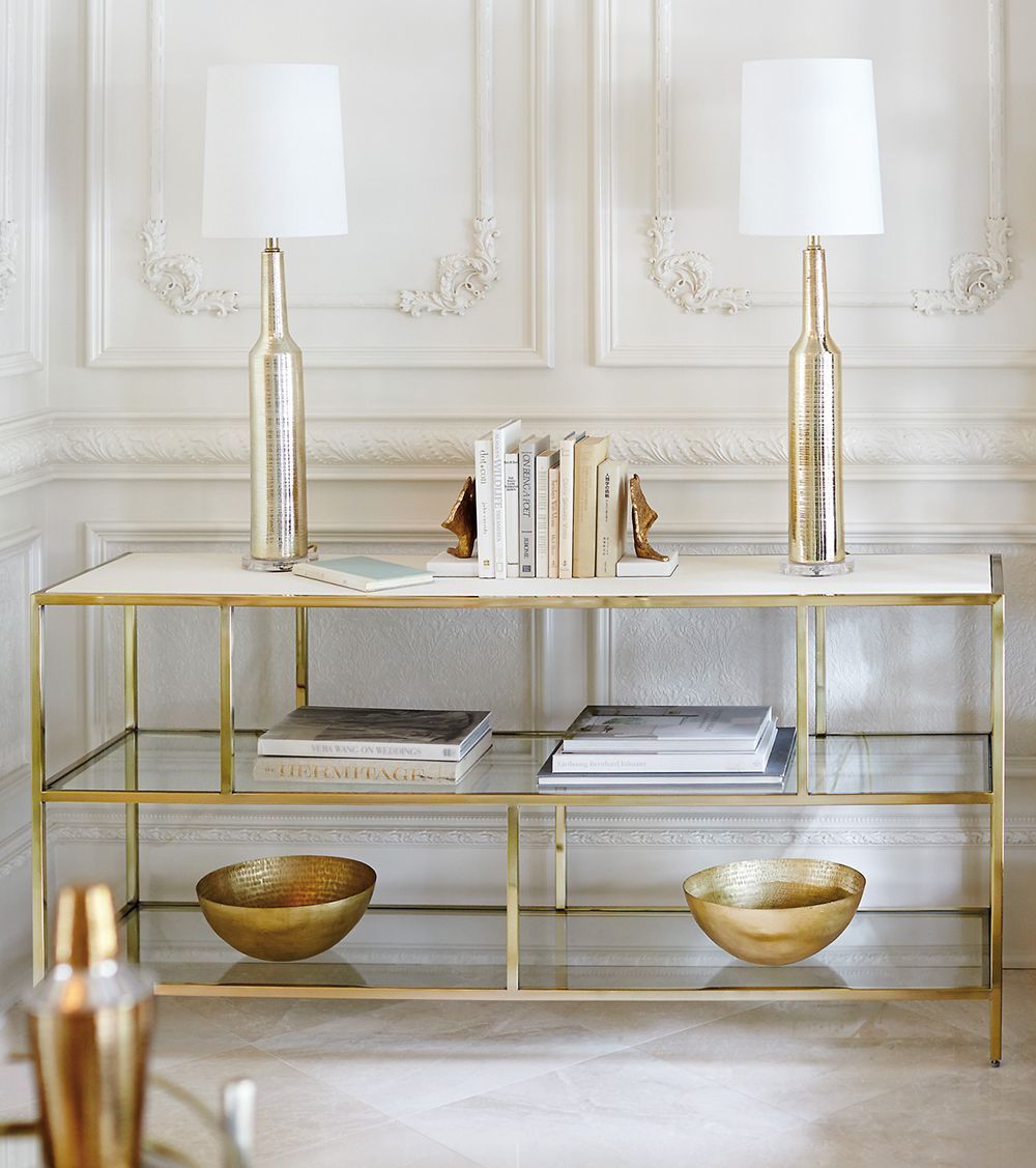 gold shelf with artful styling and two lamps
