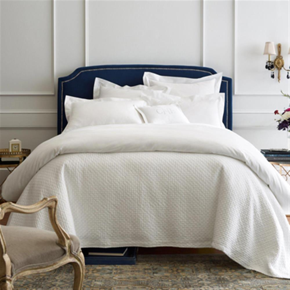chic white bed with blue headboard